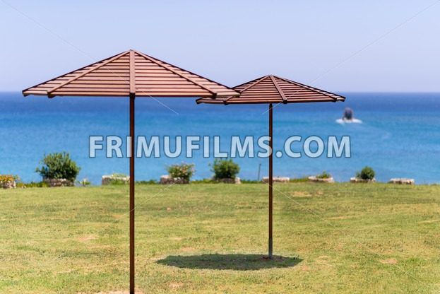 Beach umbrella on green grass at the sea in Cyprus, a boat at the horizon - frimufilms.com