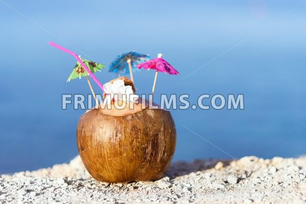 Coconut with drinking straw, umbrellas and flowers, on rocks at the sea in protaras, cyprus island - frimufilms.com