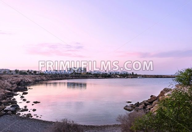 Photo of sea in protaras, cyprus island, with rocks and hotels at sunset - frimufilms.com