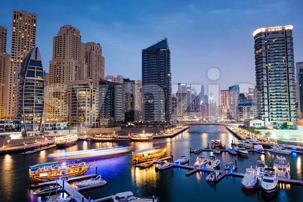 Dubai marina with boats and buildings with gates at night with lights and blue sky, United Arab Emirates